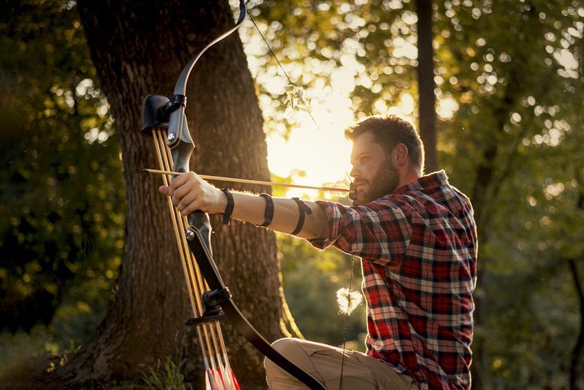 Łucznik celujący strzałę do celu w lesie
